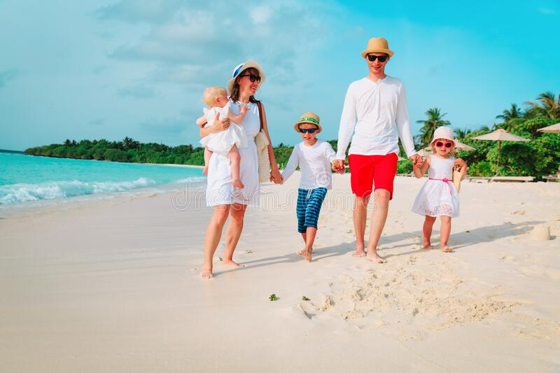 Happy family with three kids walk on beach. Happy family with three kids walk on tropical beach royalty free stock images