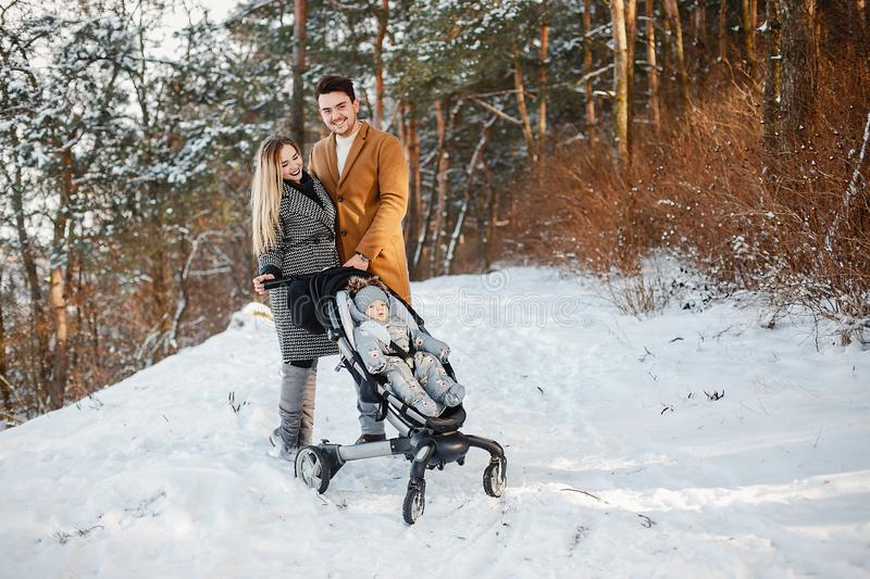 Happy family of three in the park. Happy young couple pushing a stroller in the park on a snowy winter day stock photos