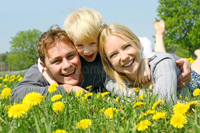 Happy Family of Three People Relaxing in Flower Meadow stock photos