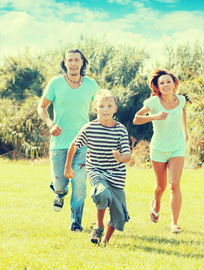 Happy family of three running on grass royalty free stock photos