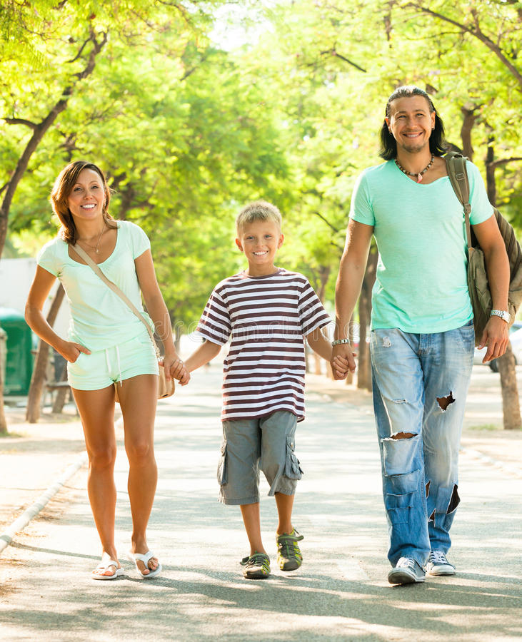 Happy family of three with teenager. Walking in summer park royalty free stock photos