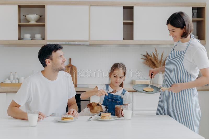Happy family time and breakfast concept. Cheerful wife and mother prepares delicious pancakes for family members, father, daughter royalty free stock photo