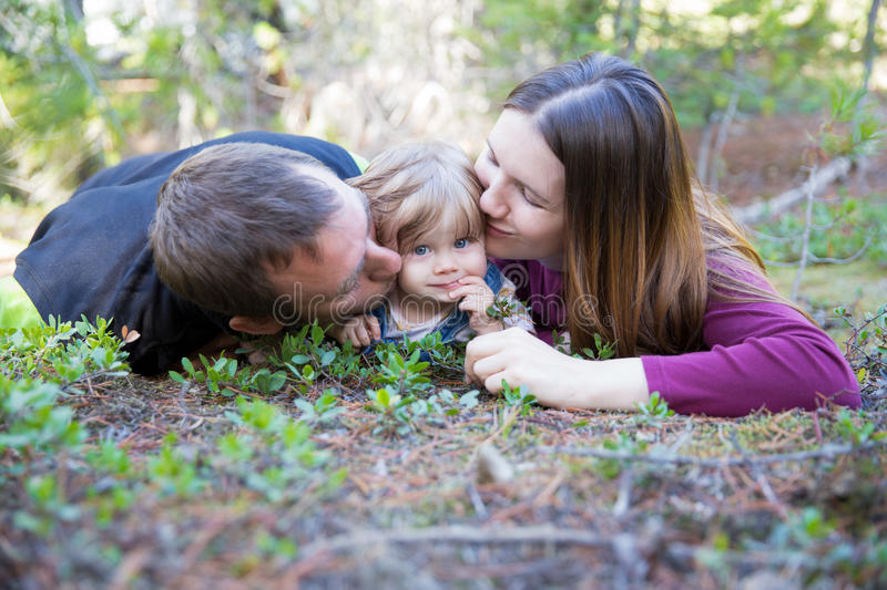 Happy family with toddler girl lying on the ground in the forest royalty free stock images