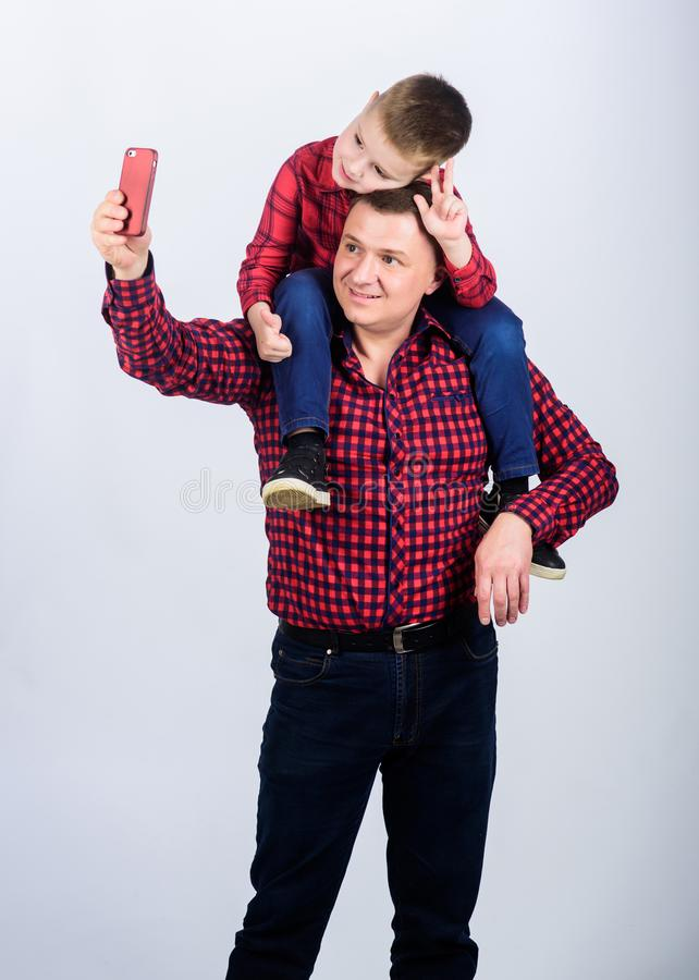 Happy family together. fathers day. Enjoying time together. childhood. parenting. father and son in red checkered shirt. Small boy with dad man. funny selfie royalty free stock photo