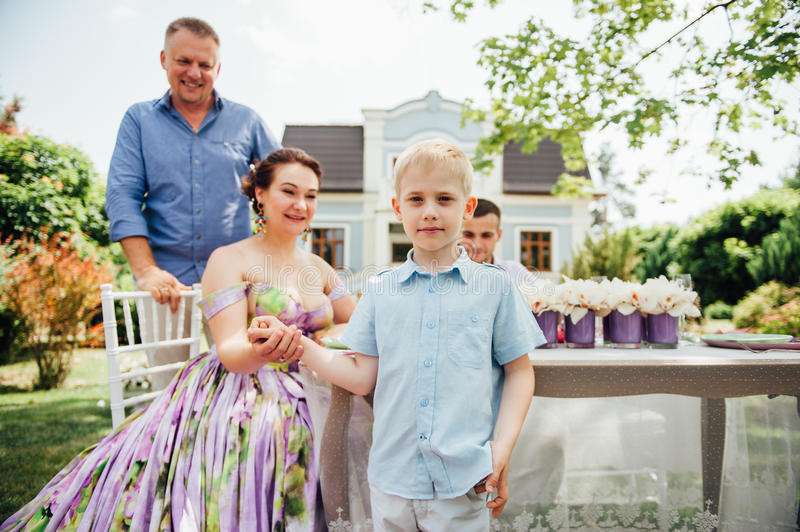 Happy family together in picnic, colorful outdoors. Father, mother and two sons. Woman in elegant long dress. Family celebrating wedding anniversary stock photo