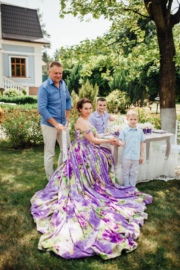 Happy family together in picnic, colorful outdoors. Father, mother and two sons. Woman in elegant long dress. Family celebrating wedding anniversary royalty free stock image