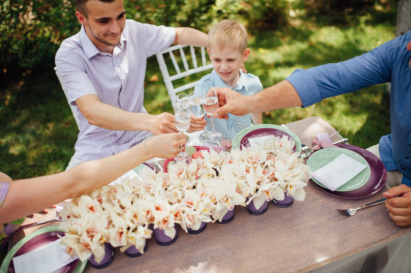 Happy family together in picnic, colorful outdoors. Father, mother and two sons. Woman in elegant long dress. Family celebrating wedding anniversary royalty free stock photos