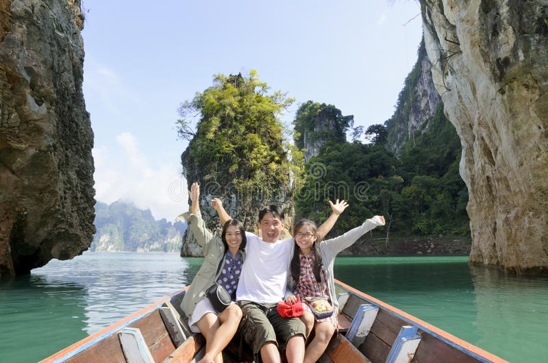 Happy family travel boat ( Guilin of Thailand ). Happy family boat trip on summer vacation in Ratchaprapha Dam, Khao Sok National Park, Surat Thani Province stock image