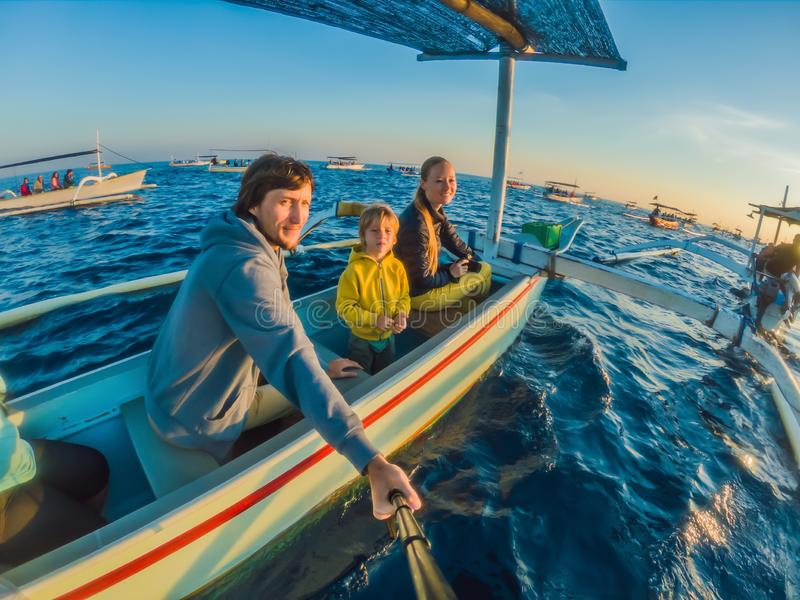 Happy family travelers meets dawn in the sea on a boat.  royalty free stock images