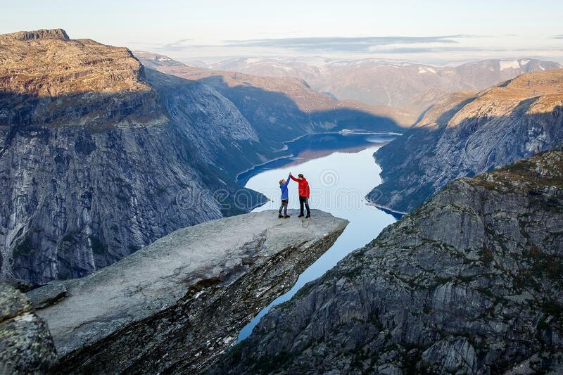 Happy family on trolltunga in Norway. Man and girl cuddle royalty free stock image