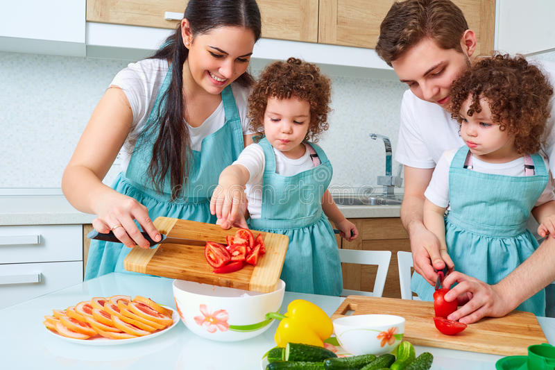 Happy family with twin daughters in the kitchen. Cheerful mother stock photo