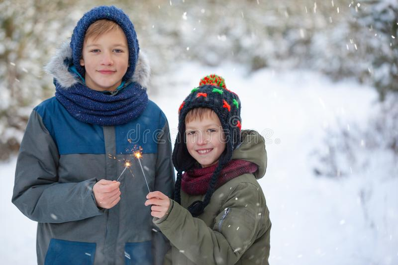 Happy family two brothers keep a sparklers or bengal fires outdoor in beautiful winter forest royalty free stock photos