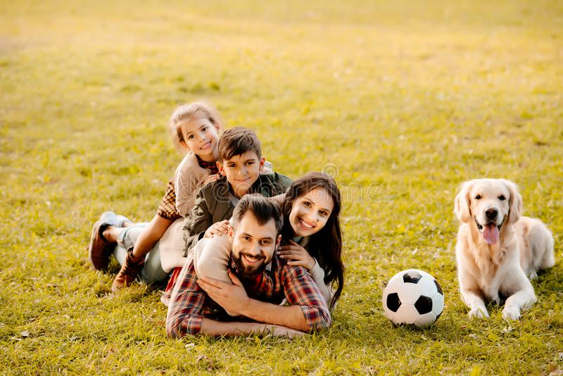 Happy family with two children lying in a pile on grass with dog sitting stock image