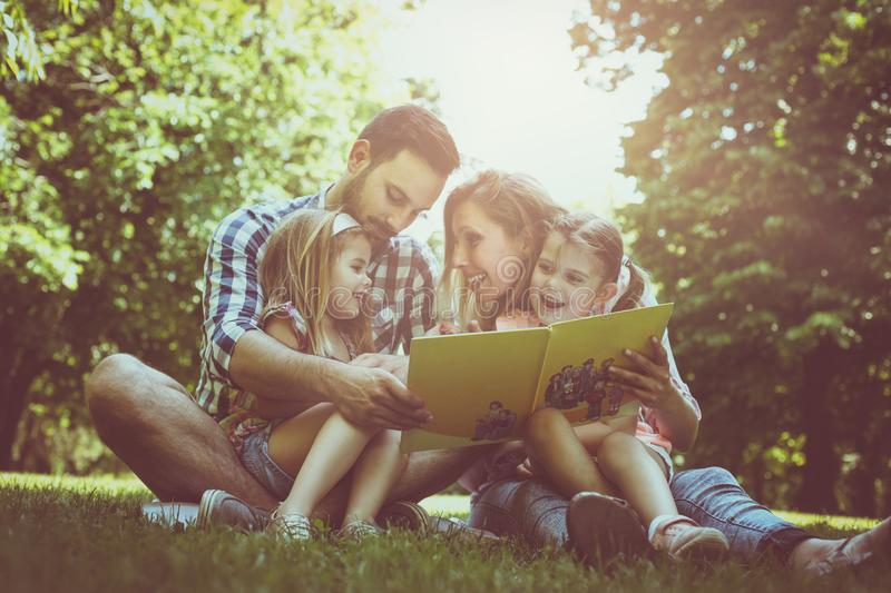 Happy family with two children in meadow reading book together. stock image