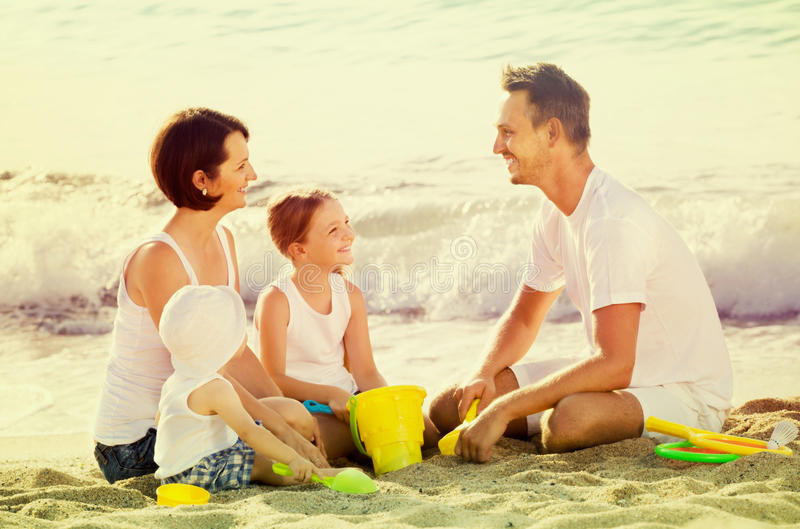 Happy family with two children playing at beach. Happy men and women with two children playing with plastic bucket and scoops at beach royalty free stock images
