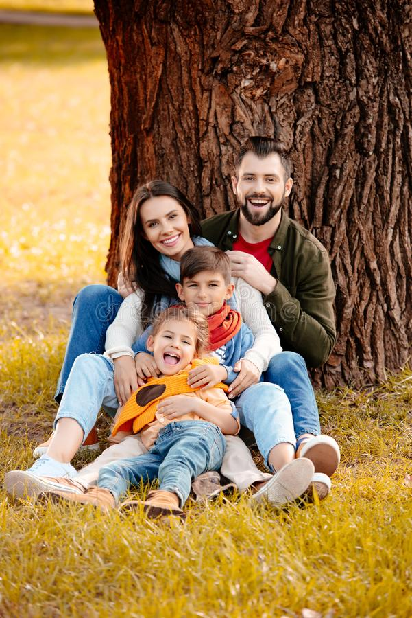 Happy family with two children sitting together on grass. In park royalty free stock image
