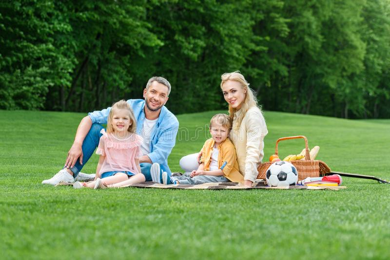 happy family with two children smiling at camera while sitting together at picnic stock images