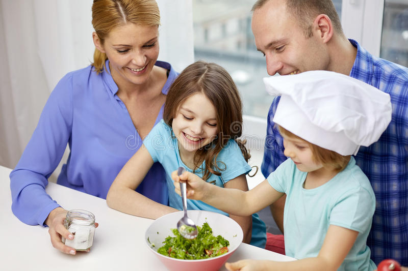 Happy family with two kids cooking at home stock photo - Bambine che cucinano ...