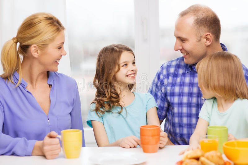 Happy family with two kids with having breakfast. Food, family, children, hapiness and people concept - happy family with two kids having breakfast at home royalty free stock photography