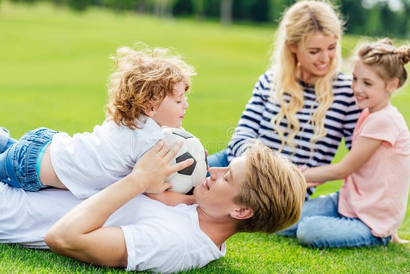 happy family with two kids having fun with soccer ball while lying royalty free stock photos