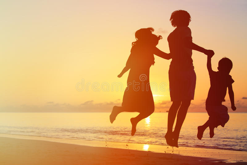 Happy family with two kids jumping at sunset. Beach stock photography