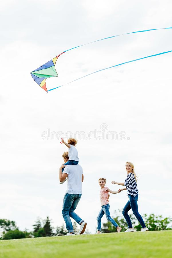 Happy family with two kids playing with kite. At park royalty free stock photos