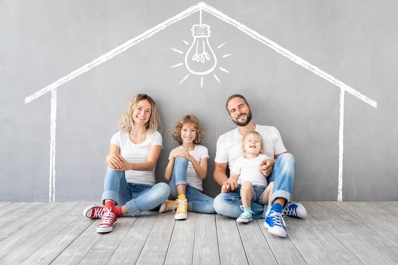Happy family with two kids playing into new home. Father, mother and children having fun together. Moving house day and real estate concept royalty free stock images