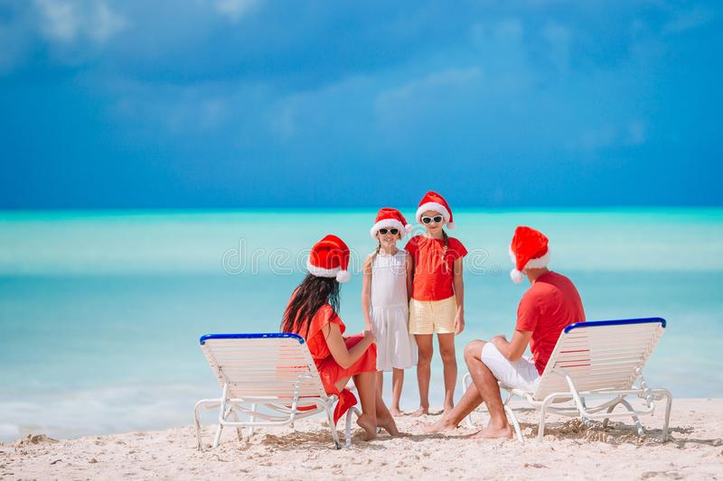 Happy family with two kids in Santa Hat on summer vacation. Happy family in Santa hats on christmas beach vacation royalty free stock images