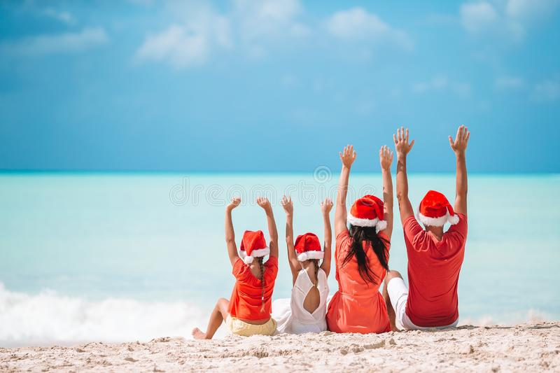 Happy family with two kids in Santa Hat on summer vacation. Happy family in Santa hats on a tropical beach celebrating Christmas vacation royalty free stock photos