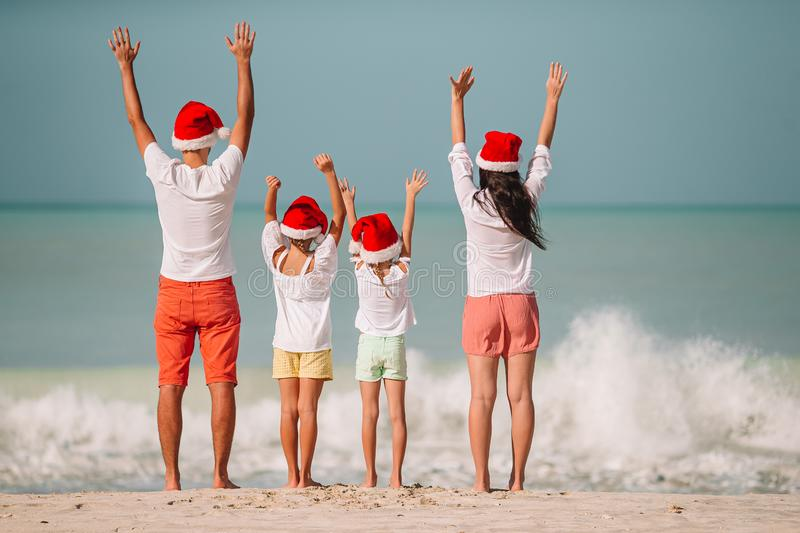 Happy family with two kids in Santa Hat on summer vacation. Happy family in Santa hats on a tropical beach celebrating Christmas vacation stock images