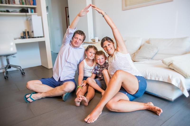 Happy family with two kids sitting on floor making roof figure with hands stock photo