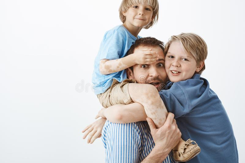Happy family of two sons and father gazing and smiling at camera. Dad holding cute kid with vitiligo on shoulders while. Older brother hanging on chest, having royalty free stock image