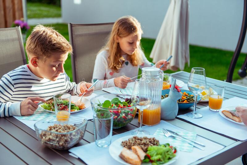 Happy family with two teen children eating healthy dinner together on terrace stock photos