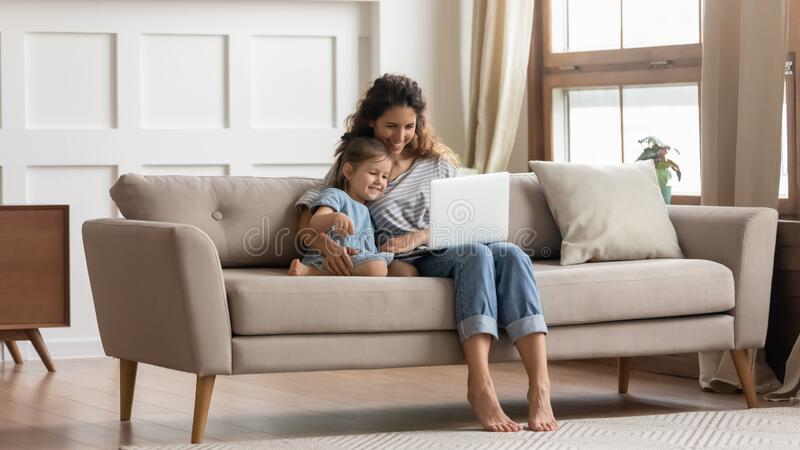 Happy family of two watching comedy movie cartoons on laptop. Full length attractive young mommy embracing small preschool daughter, making purchases in royalty free stock image
