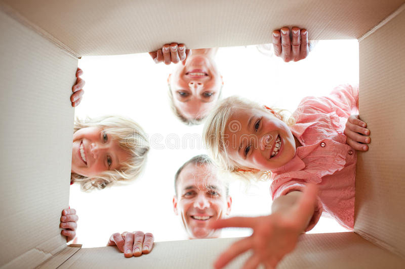 Happy family unpacking boxes stock image