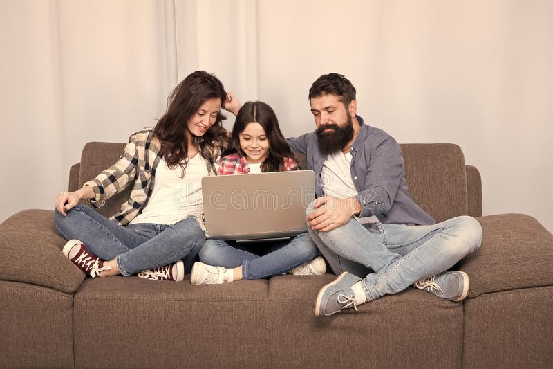 Happy family using laptop. Stay online. little girl with parents. mother and bearded father with daughter looking at royalty free stock image