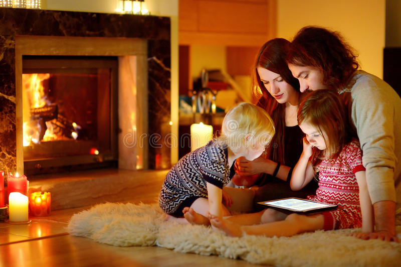 Happy family using a tablet pc by a fireplace. Happy young family using a tablet pc at home by a fireplace in warm and cozy living room on winter day stock photo