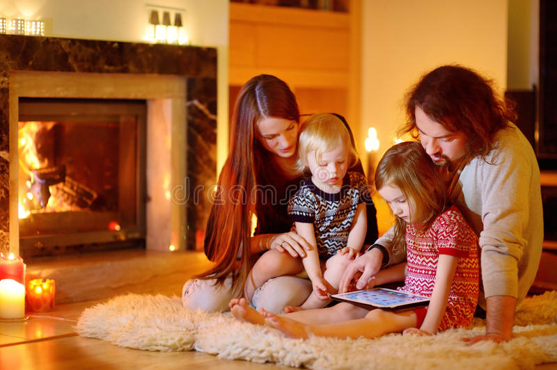 Happy family using a tablet pc by a fireplace. Happy young family using a tablet pc at home by a fireplace in warm and cozy living room on winter day stock photos