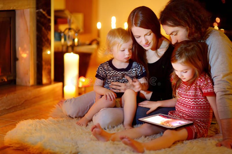 Happy family using a tablet pc by a fireplace. Happy young family using a tablet pc at home by a fireplace in warm and cozy living room on winter day stock image