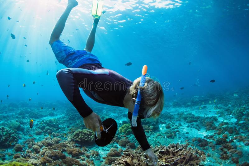 Young man in snorkelling mask dive underwater. Happy family vacation. Man in snorkeling mask with camera dive underwater with tropical fishes in coral reef sea stock image