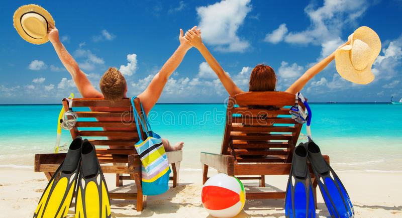 Happy family vacation at Paradise. Couple relax on the white sand of beach. Happy sea lifestyle. Young family, man and woman rest. Happy family vacation at stock photo
