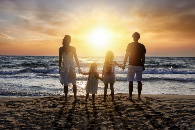 Happy family on vacation stands on the beach. Hand in hand an enjoys the romantic sunset over the sea royalty free stock image