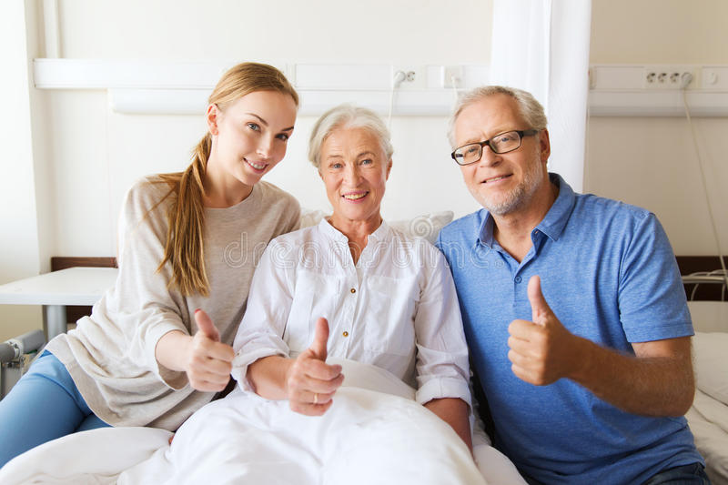 Happy family visiting senior woman at hospital. Medicine, family support, gesture, health care and people concept - happy senior men and young women visiting her royalty free stock images