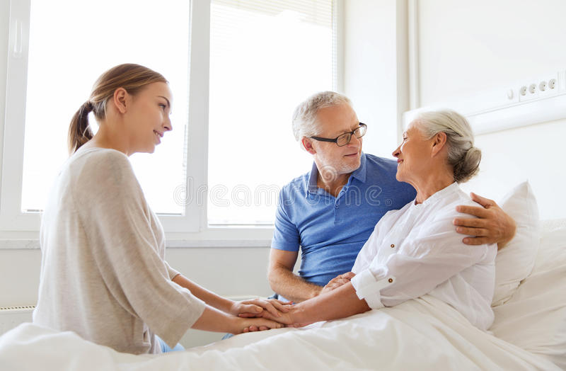Happy family visiting senior woman at hospital. Medicine, support, family health care and people concept - happy senior men and young women visiting and cheering royalty free stock image