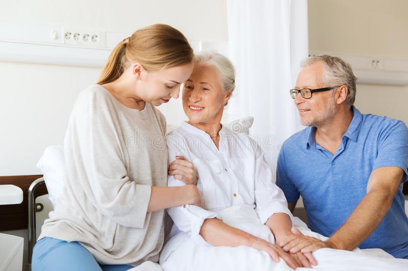 Happy family visiting senior woman at hospital. Medicine, support, family health care and people concept - happy senior men and young women visiting and cheering stock photo
