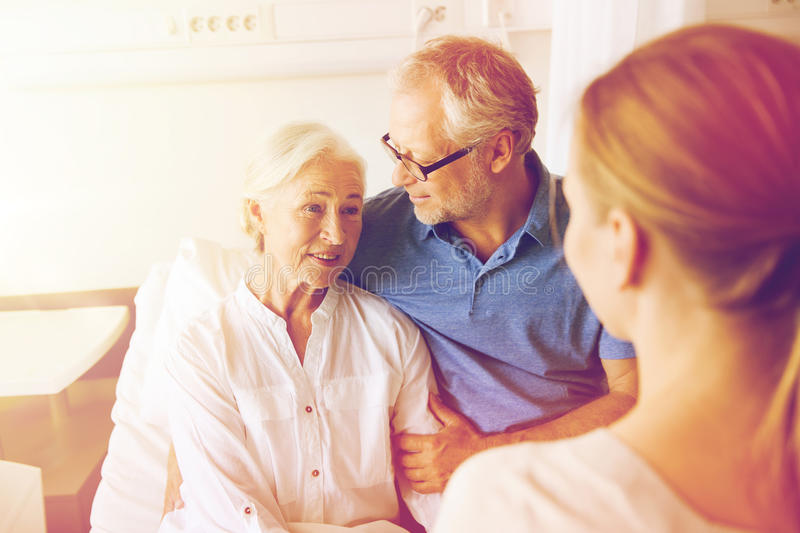 Happy family visiting senior woman at hospital. Medicine, support, family health care and people concept - happy senior men and young women visiting and cheering royalty free stock photos