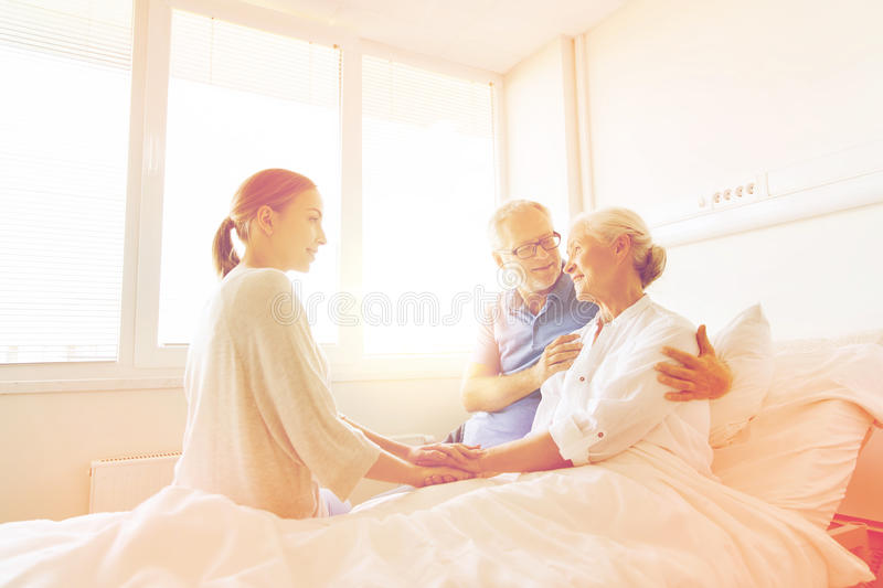 Happy family visiting senior woman at hospital. Medicine, support, family health care and people concept - happy senior men and young women visiting and cheering royalty free stock photo