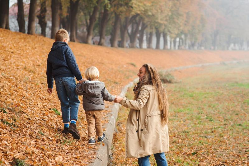 Happy family on a walk in autumn park. Young mother with her sons enjoying autumn weather. Happy autumn holidays. Motherhood, royalty free stock photos