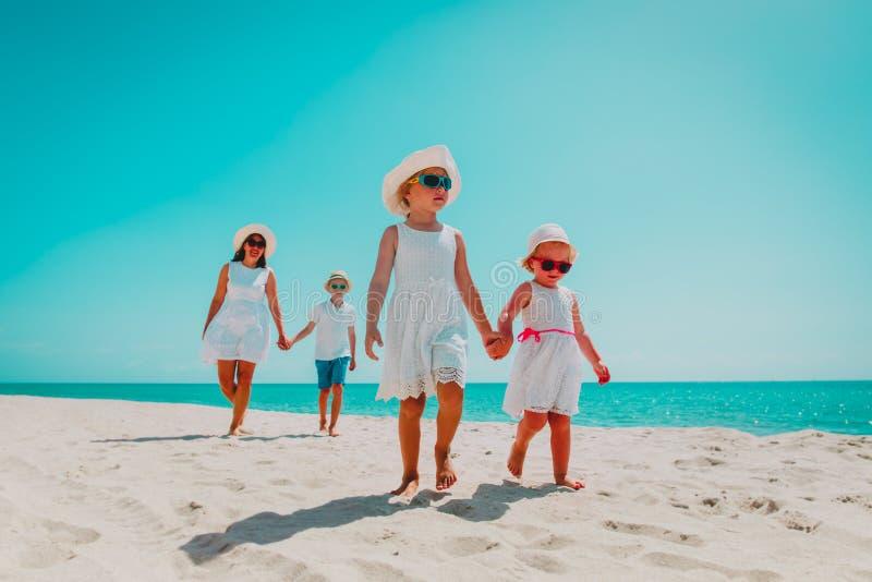 Happy family walk on beach, mother with kids enjoy sea stock photo