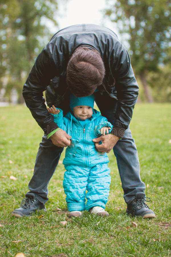 Happy family walking in autumn park: father and his little son - learn to stand independently royalty free stock photos
